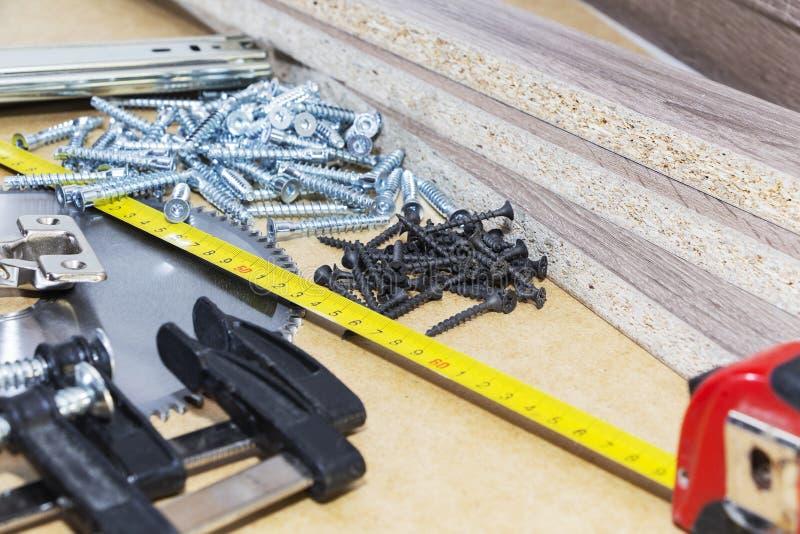 Жесты, подтверждения на мебель, лента мера, зажим, лежат на столе Производство мебели стоковые изображения rf