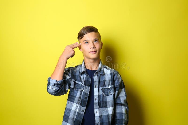 Жест пистолета руки показа подростка на предпосылке цвета стоковые фотографии rf