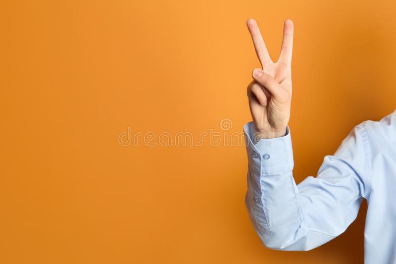 Жест победы показа молодой женщины на предпосылке цвета стоковая фотография
