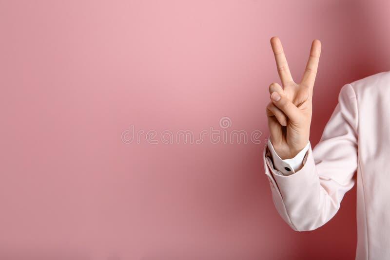 Жест победы показа молодой женщины на предпосылке цвета стоковые изображения rf
