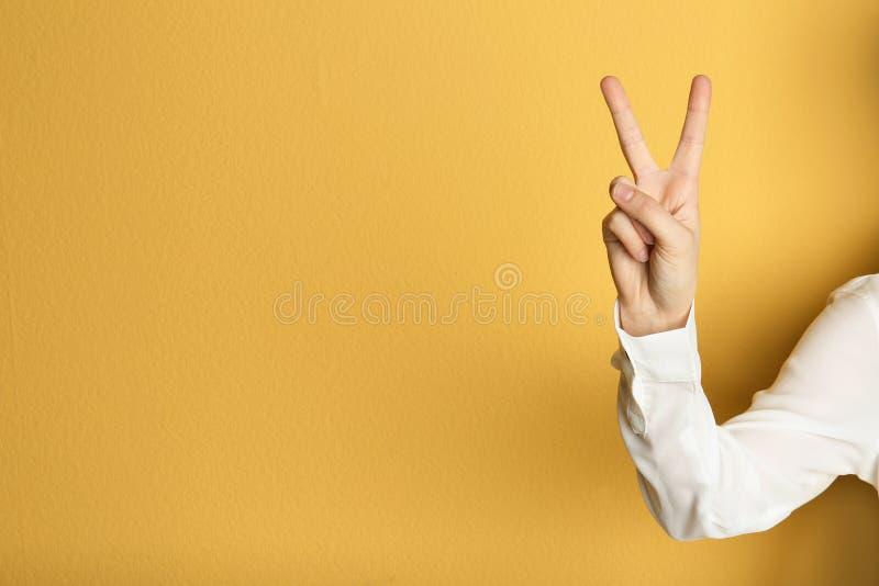 Жест победы показа молодой женщины на предпосылке цвета стоковое фото