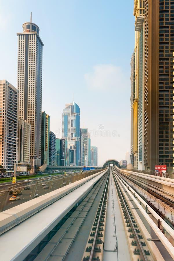 Железная дорога метро Дубай, с ультра современными зданиями highrise дальше стоковые изображения