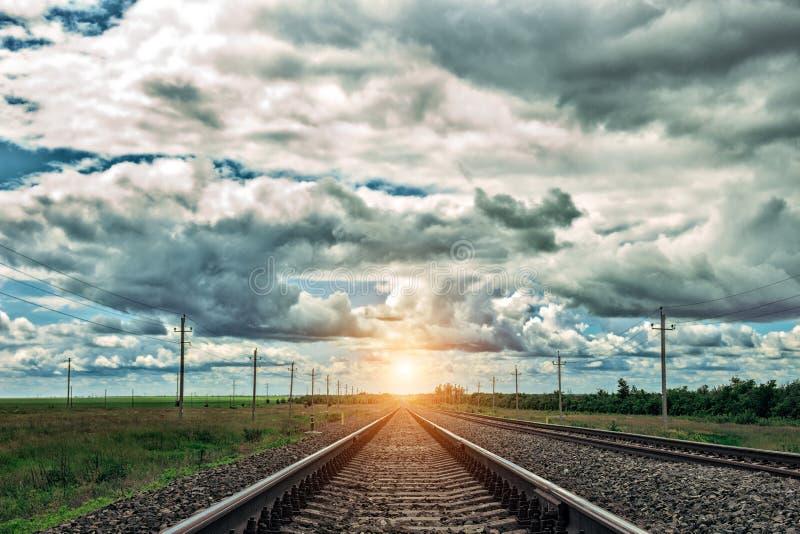 Железная дорога на заходе солнца с драматическим небом След железной дороги стоковые изображения
