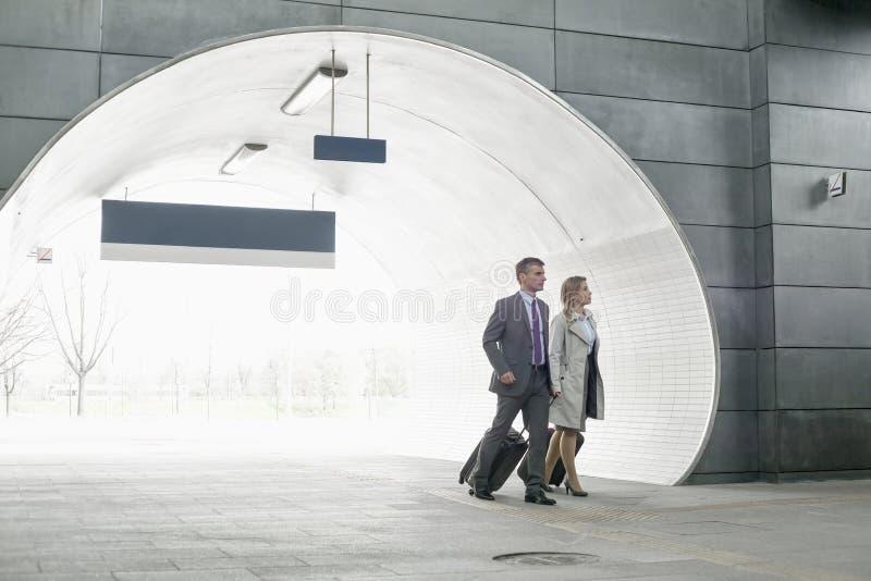 Железнодорожная станция бизнесмена и коммерсантки входя в стоковое фото