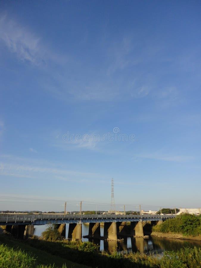 Железнодорожный мост над рекой Kokai с небом осени голубым стоковое фото rf