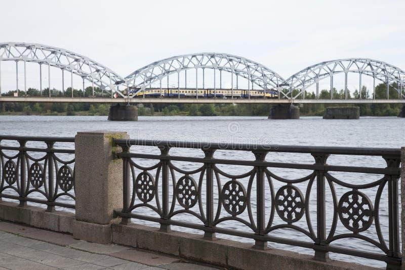 Железнодорожный мост с поездом и банками западной Двины реки, Риги стоковая фотография