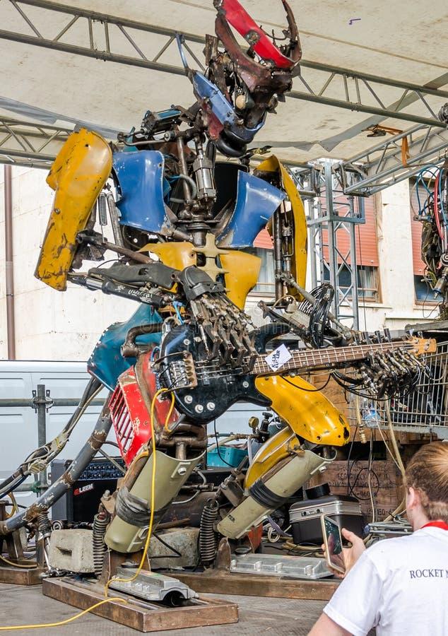 Железный гигантский музыкант робота, собранный от больших кусков металла от сброса, играет гитару, управляя вашим компьютером, на стоковая фотография rf