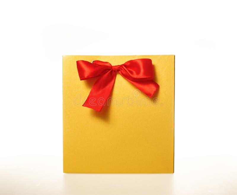 Желтая бумажная сумка подарка с красной лентой на белой предпосылке стоковое фото