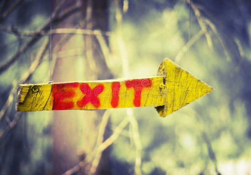 Желтая деревянная металлическая пластинка в форме стрелки с выходом слова в взбираясь лес или парк натянутой проволоки на предпос стоковые фото