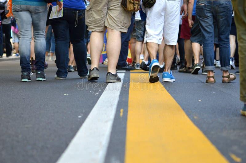 Желтая линия при толпы идя вперед стоковое фото