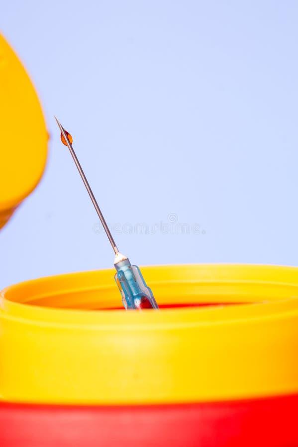 Желтая медицинская коробка отхода избавления, игла шприца с красным падением на подсказке стоковые фото