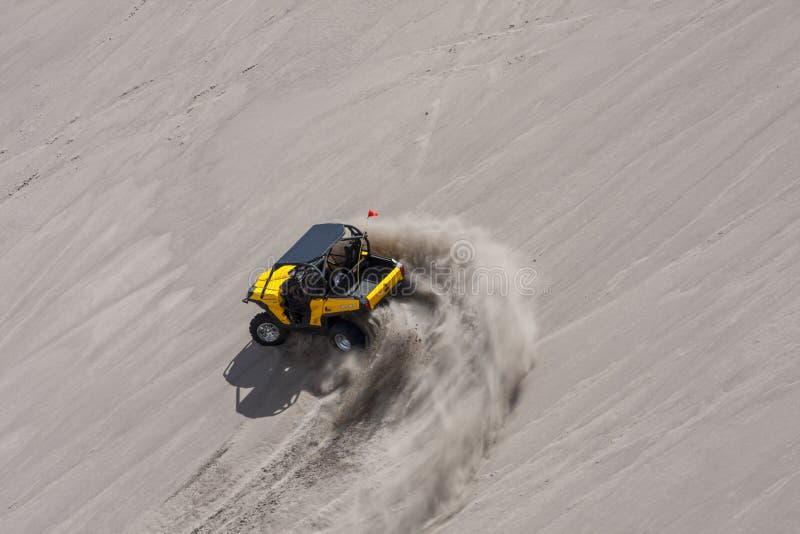 Желтая сторона - мимо - бортовые дефектные гонки мимо в песчанных дюнах стоковые изображения rf