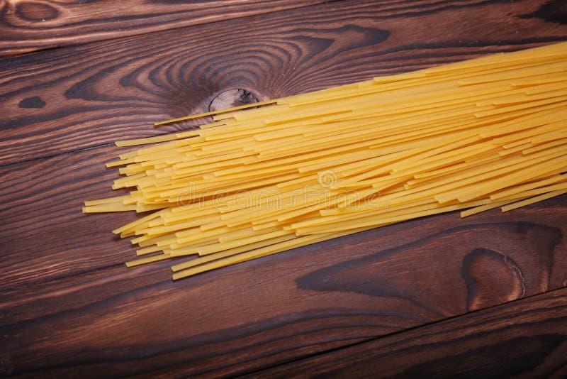 Желтые лапши на деревянной предпосылке Сырые спагетти на таблице Длинние макаронные изделия Традиционные среднеземноморские ингри стоковая фотография