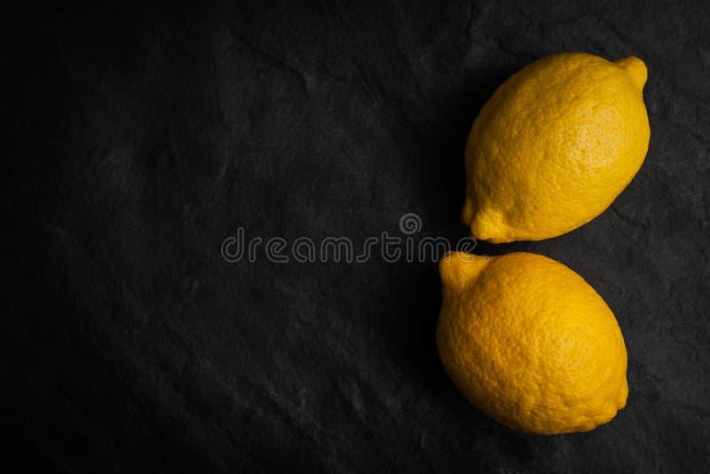 Желтые лимоны на черной каменной таблице горизонтальной стоковое изображение rf