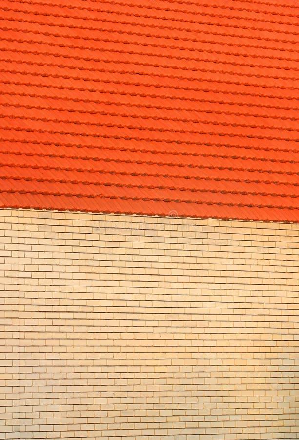 Желтые кирпичная стена и апельсин крыли крышу черепицей как предпосылка стоковое изображение rf