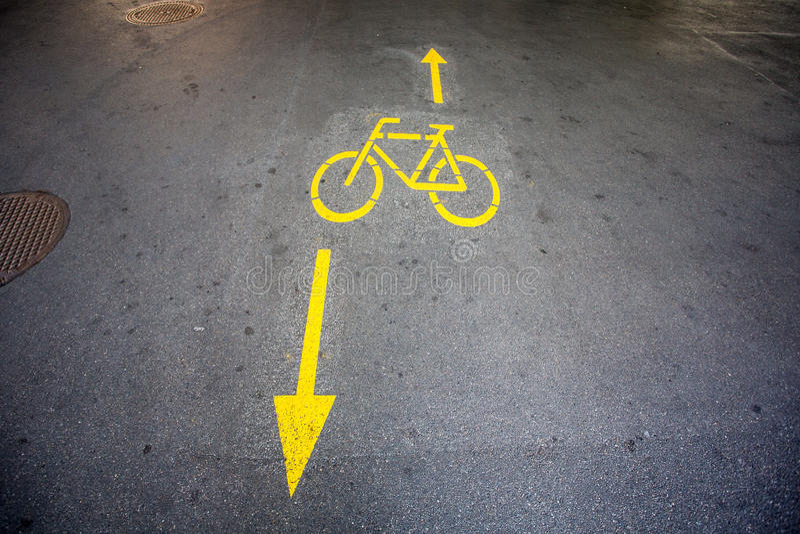 Желтые стрелки и велосипед подписывают путь на дороге стоковые изображения rf