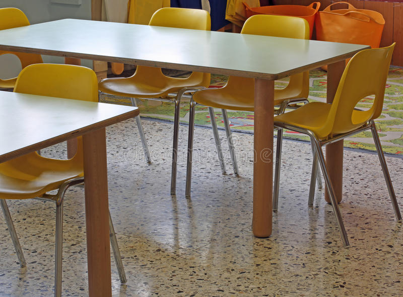 Желтые стулья и малая школа детского сада таблиц стоковое фото