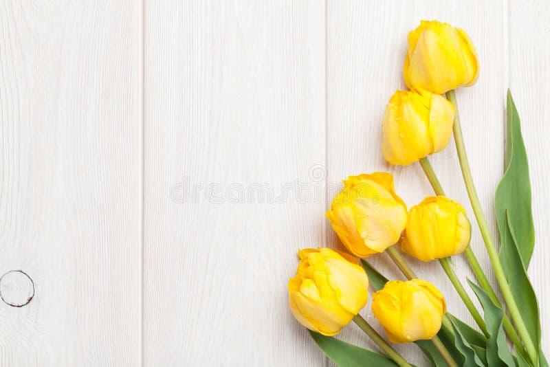 Желтые тюльпаны над деревянным столом стоковое фото