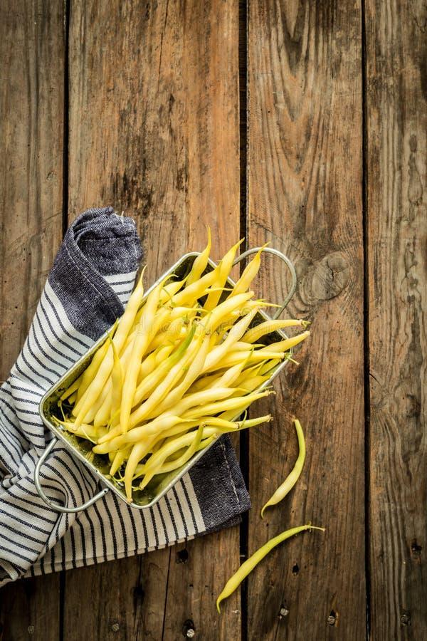 Желтые фасоли (французские фасоли) на деревянном сельском кухонном столе стоковое фото rf