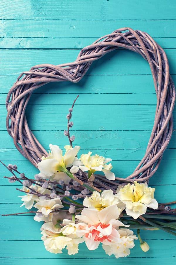 Желтые daffodils, ветви вербы и декоративное сердце на tur стоковые изображения