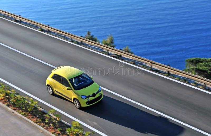 Желтый автомобиль двигая дальше дорогу стоковое изображение