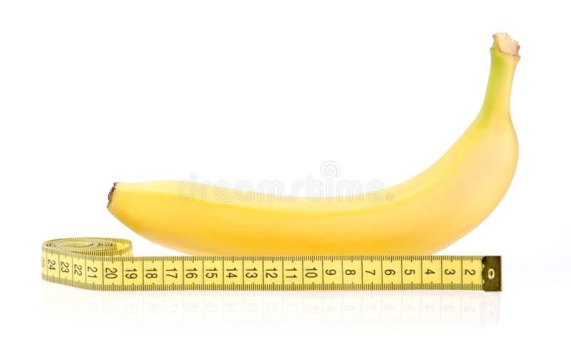 Желтый банан с измеряя лентой стоковые фотографии rf