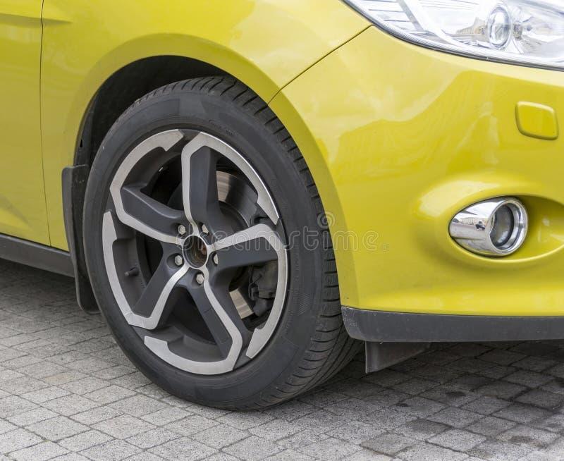 Желтый крупный план автомобиля - переднее колесо с оправой светлого сплава стоковые фотографии rf