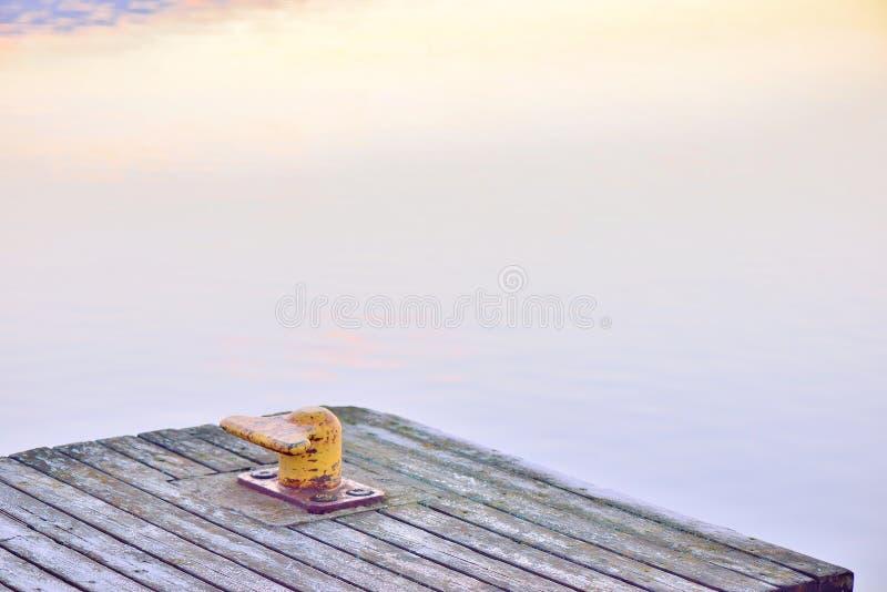 Желтый пал, или столб гавани, на деревянной пристани стоковое изображение rf