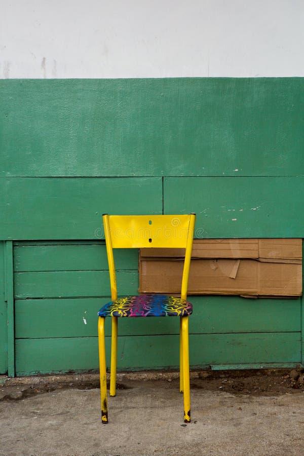 Желтый старый металлический стул с деревянной предпосылкой стоковые изображения rf