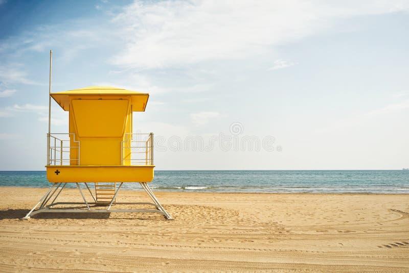 Желтый столб личной охраны на пустом пляже стоковое фото rf