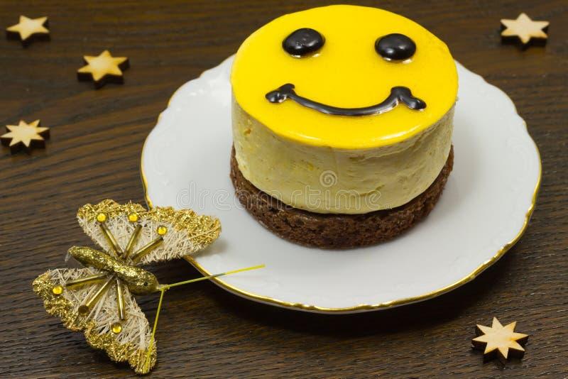 Желтый торт с глазами и ртом; На темном butterfl предпосылки стоковое фото