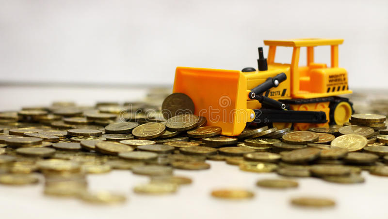 Желтый трактор сгребая вверх по монеткам Русская рублевка стоковые изображения