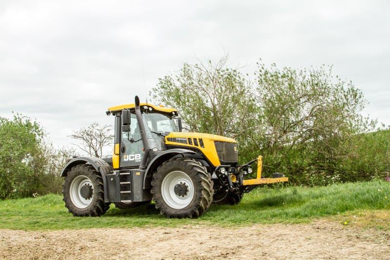 Желтый трактор JCB Fastrac припаркованный изгородью стоковая фотография