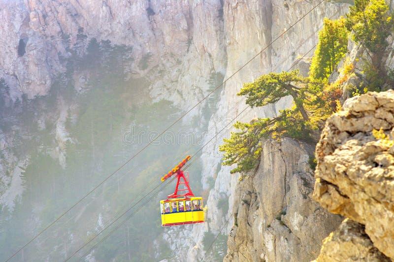 Желтый фуникулярный кабель с кабиной высокой с скалистыми горами на предпосылке стоковые изображения