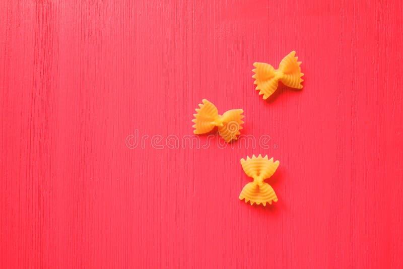 Желтый цвет макаронных изделий обхватывает на яркой розовой деревянной предпосылке стоковая фотография