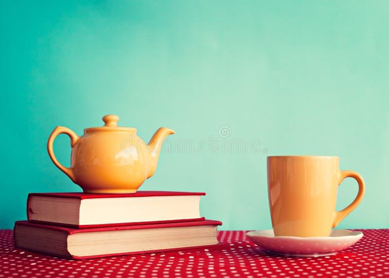 Желтый чайник над книгами стоковое изображение
