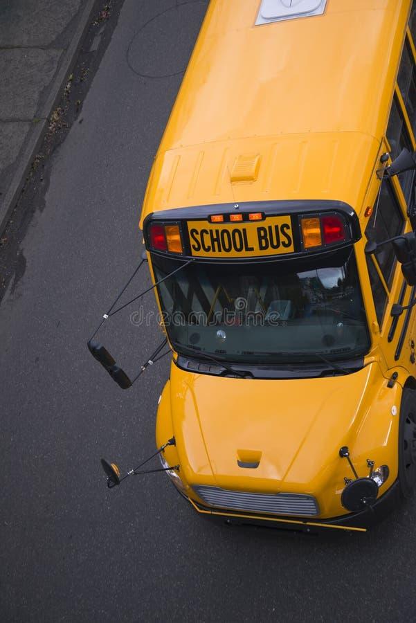 Желтый школьный автобус на дороге носит школьников стоковое изображение