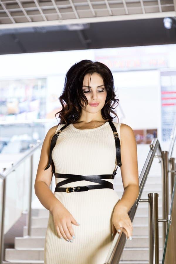 Живите полно Славные красивые покупки молодой женщины пока идущ через мол девушка идет вниз с лестниц стоковые фото