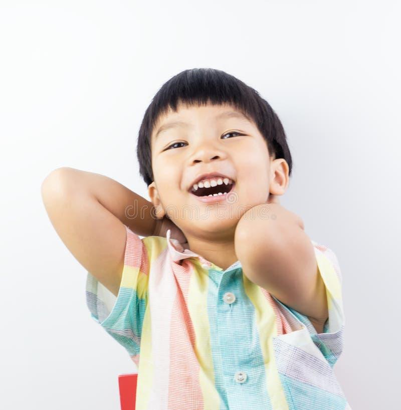 Живой азиатский мальчик смеется над счастливо на белизне стоковые изображения