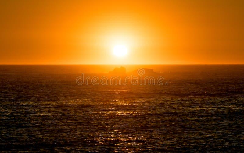 Живой оранжевый заход солнца на океане с отражениями на поверхности и утесах воды в силуэте стоковые изображения rf