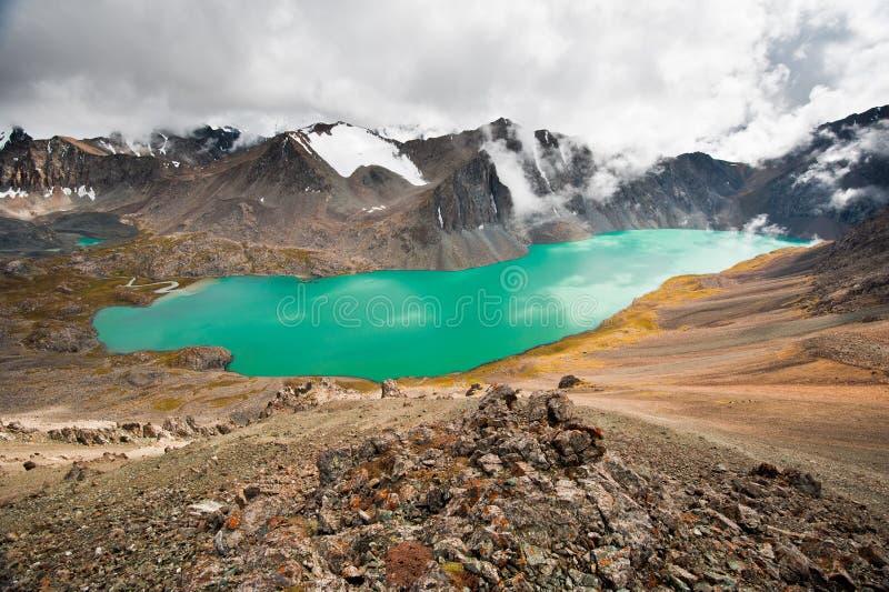 Живописная ала-Kul озера горы бирюзы Озеро Alakol с облачным небом Snowboarder сидя вниз на снежке kyrgyzstan стоковая фотография