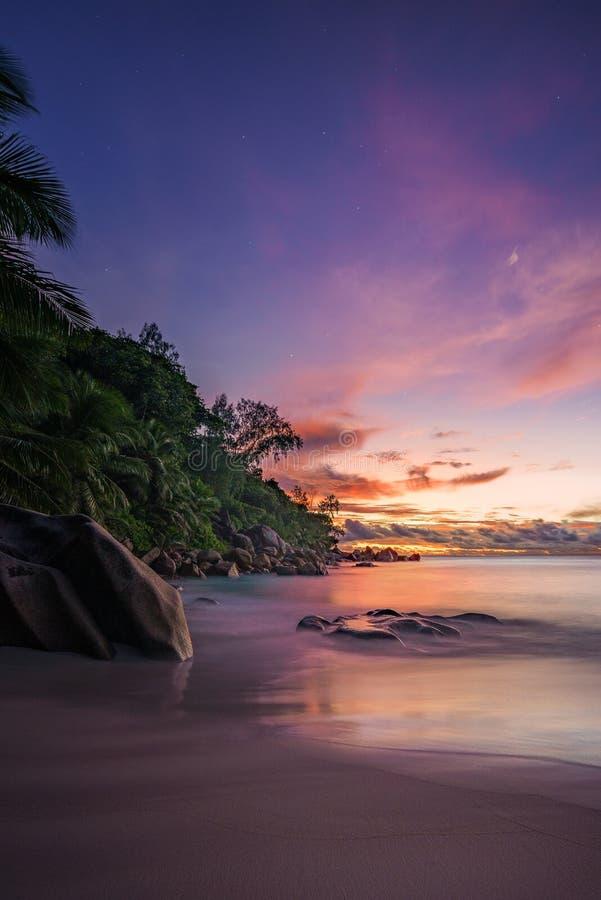Живописное красное небо после захода солнца на пляже рая на Сейшельских островах 4 стоковое фото rf