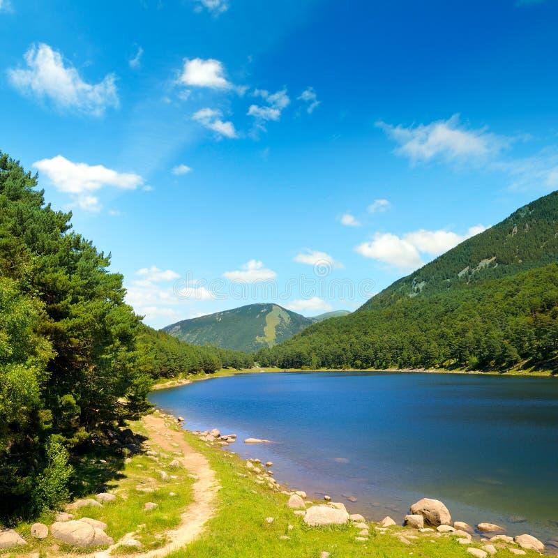 Живописное озеро, горы и голубое небо стоковые изображения