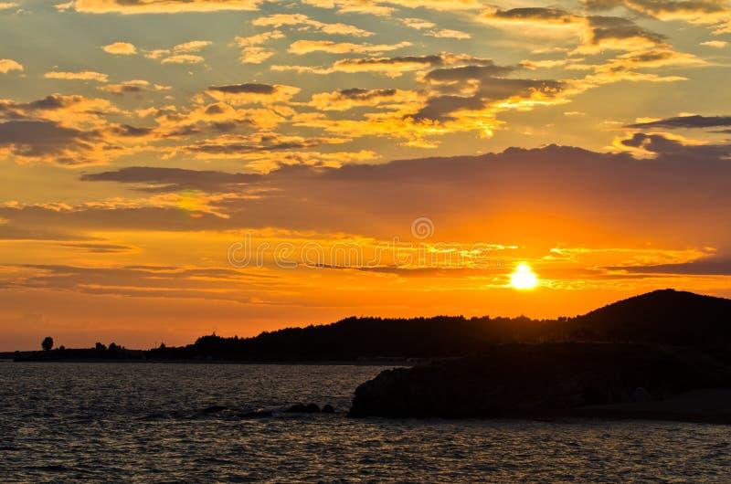 Живописное cloudscape с силуэтом моря трясет на заходе солнца стоковое изображение