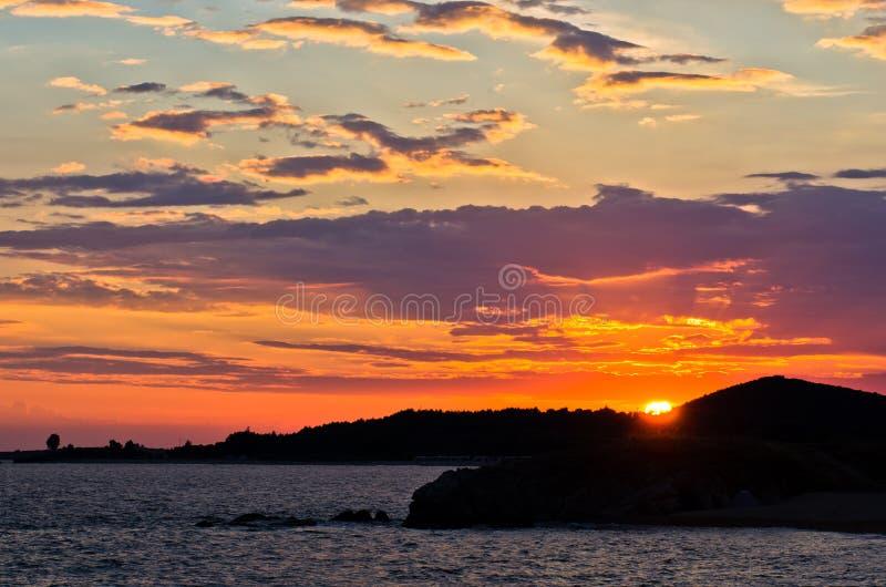 Живописное cloudscape с силуэтом моря трясет на заходе солнца стоковое фото