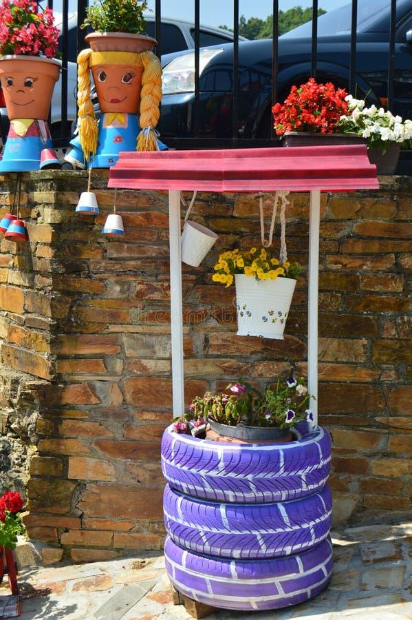 Живописные баки украсили как 2 молодых Asturians рядом с колодцем воды также украшенным с фиолетовыми автошинами в Taramundi, Аст стоковая фотография rf