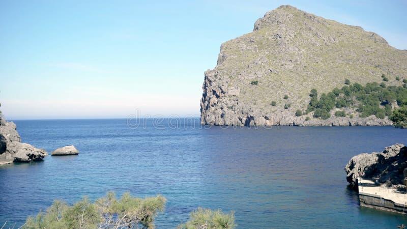 Живописный взгляд берега голубого моря и зеленой горы скалистого r Красивый seascape со скалистыми скалами покрытыми с стоковое изображение rf