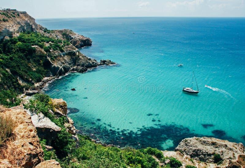 Живописный взгляд голубого чистого моря, утесов и зеленых деревьев E стоковая фотография rf