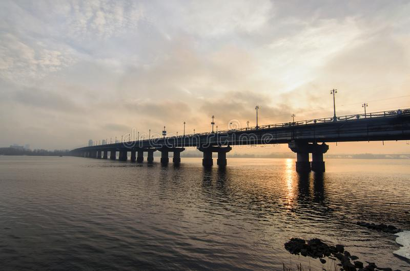 Живописный взгляд над мостом ` s Paton над рекой Dnieper во время восхода солнца зимы Солнце отразило в воде Kyiv, Украин стоковая фотография rf