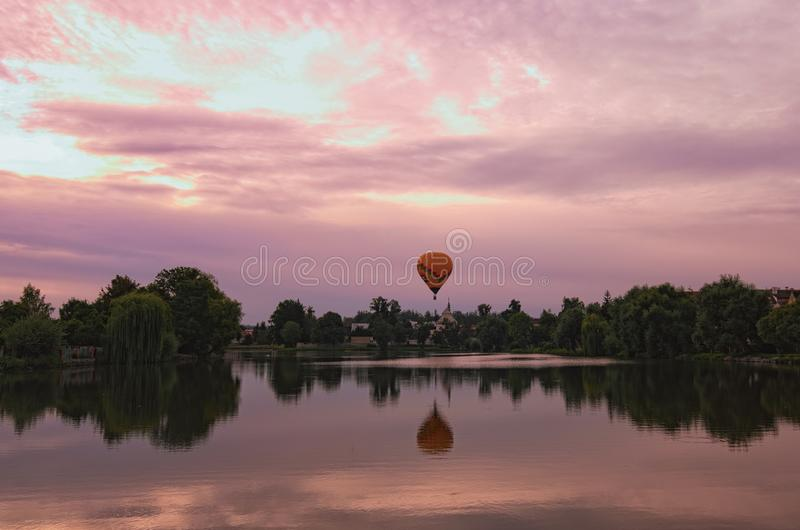 Живописный взгляд средневекового Telc во время волшебного восхода солнца Один горячий воздушный шар летает над домами и отразил н стоковая фотография